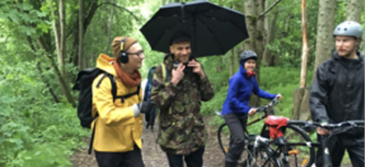 Neljä henkilöä metsäpolulla, oikeassa reunassa kahdella on polkupyörät ja pyöräilykypärät. Vasemman puoleisella on kuulokkeet korvilla ja keltainen sadetakki päällä. Keskellä olevalla henkilöllä on maastokuvioinen takki ja musta sateenvarjo.