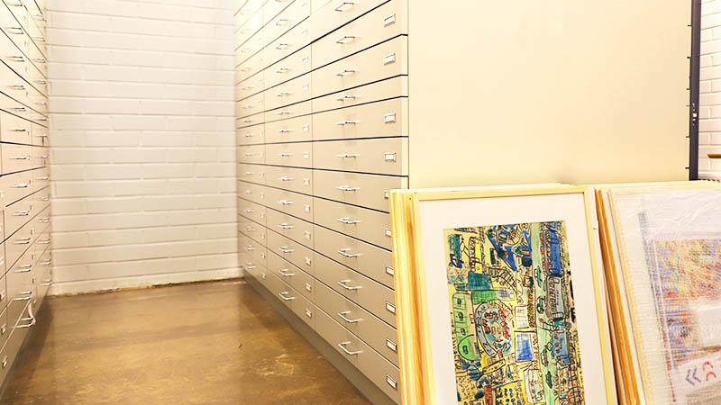 Tyhjä käytävä, jonka molemmin puolin korkeat laatikostot. Oikean puoleisen laatikoston etualaan nojaa kehystettyjä teoksia kahdessa pinossa. Oikean puoleisen pinon työt on niputettu yhteen kiristyskemulla.