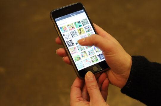 Puhelin, josta kaksi kättä pitää kiinni. Näytöllä näkyy pieniä neliön muotoisia kuvia.