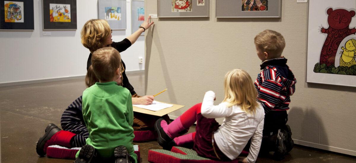 Neljä lasta ja aikuinen katsovat yhdessä seinällä olevaa taideteosta ja lukevat teostietoja taulun vieressä olevalta teoskortilta.