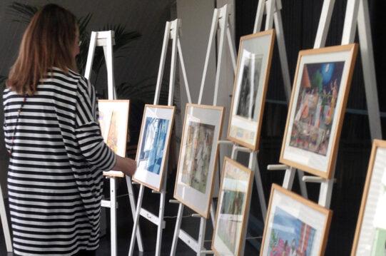 Henkilö seisoo maalaustelineiden edessä. Maalaustelineillä on tauluja. Etualalla olevan taulun teos näkyy, siinä on tummahiuksisia henkilöitä potrettimaisesti.