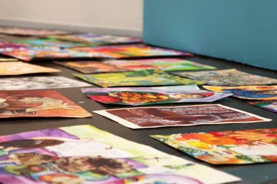 Teoksia lattialla niin, ettei niiden sisällöistä saa tarkasti selvää. Kuva teoksista on otettu sivulta päin ja siitä johtuen osa teoksista näyttää, että osa teoksista leijuu lattian pinnan yläpuolella.
