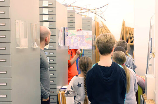 Ihmisiä arkistossa. Oikeassa laidassa peräkkäin laatikostoja, joiden väleissä näkyy muutamia henkilöitä. Yksi henkilöistä on näyttää teosta. Takaseinällä näkyy pystyssä tauluja.
