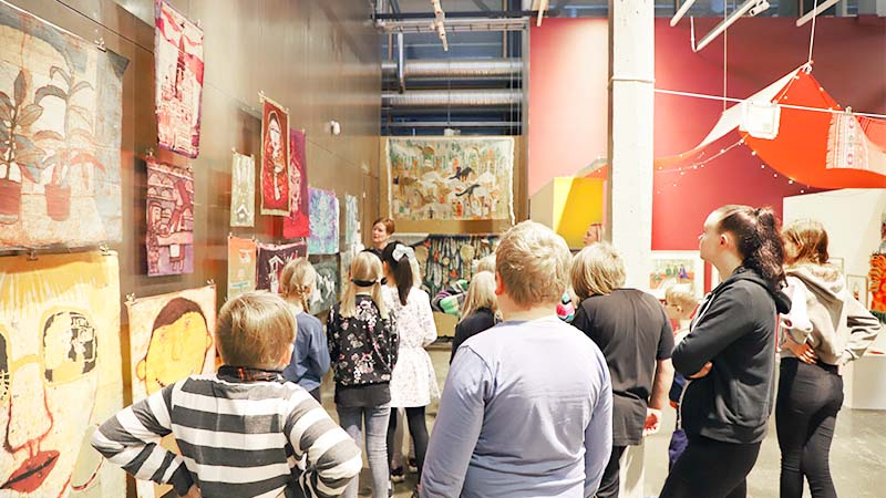 Ryhmä lapsia opastuksella näyttelyssä. Opas on pystähtynyt ryhmän kanssa seinävaatteiden, eli batiikkien kohdalle. Batiikkeja on usessa eri tasossa ja ne roikkuvat metallisen seinän edessä.