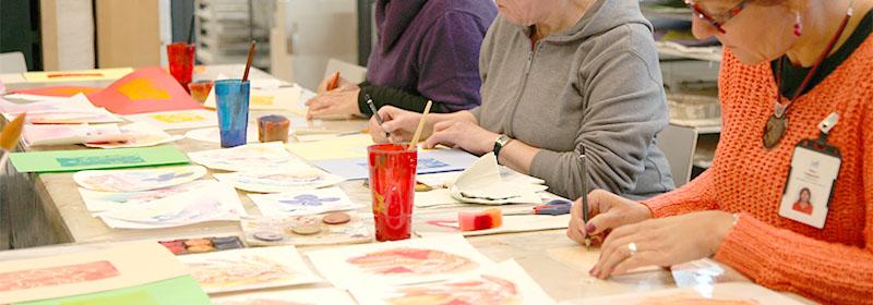Pöytä, jonka äärellä kolme henkilöä piirtää tai kirjoittaa puukynällä. Pöydän päällä eri värisiä papereita, joihin on maalattu eri väreillä. Jokaisen henkiön edessä on korkea muki, jossa on sivellin.