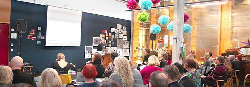 Kuva on otettu yleisön selän takaa ja lavalla puhuu vaalea hiuksinen henkilö. Tilassa katosta roikkuu eri värisiä pompuloita ja puhujan takana seinällä on paljon eri kokoisia teoksia ilman kehyksiä.