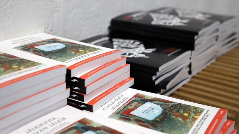 Kirja pinoja. Etualalla olevat pinot ovat kirjasta Jälkikuvia, kuvan jälkiä ja taka-alalla olevat pinot Taidejemmoja – Taidetta, tallennusta ja tutkimusta.