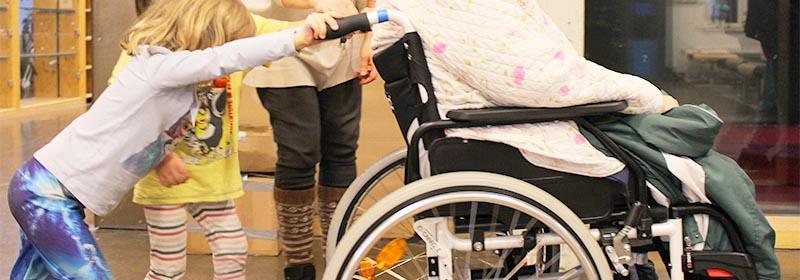 Lapsi työntää pyörätuolissa olevaa henkilöä.