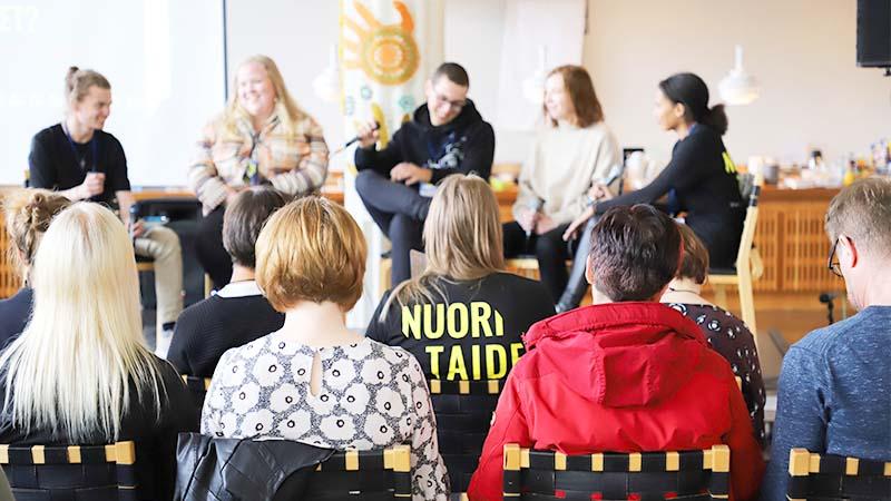 """Lavalla viisi nuorta henkilöä. Yleisö seuraa mitä lavan ohjelmaa ja keskellä yleisöä yhdellä henkilöllä päällää paita, jonka selässä isolla teksti """"Nuori Taide""""."""